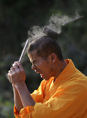 A shaolin monk breaks an iron sheet with his head during a performance at a temple in Quanzhou